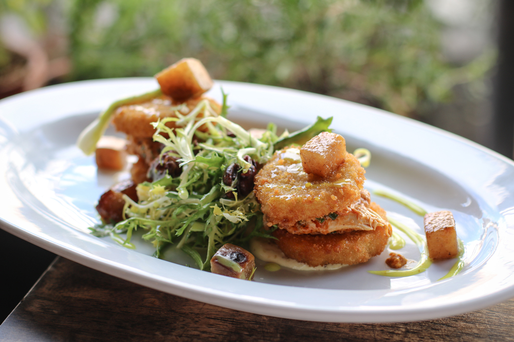 This is the smoked chicken salad at The Local in Coral Gables, Florida. It has fried green tomatoes, mixed greens, pears, pecans, a vinaigrette and smoked chicken of course!