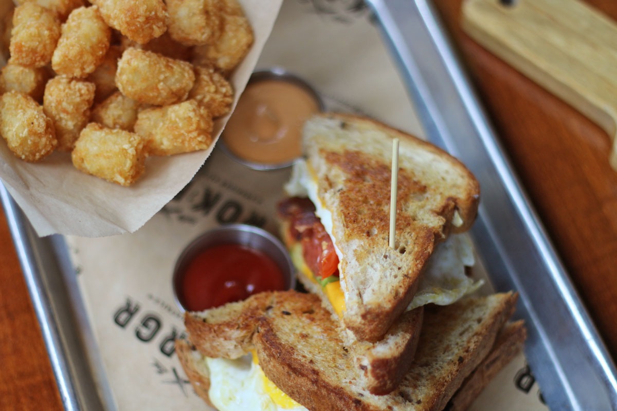ROK:BRGR South Miami Saturday Brunch Hangover Sandwich with eggs, bacon, avocado, tomato, and cheese served with crispy tater tots